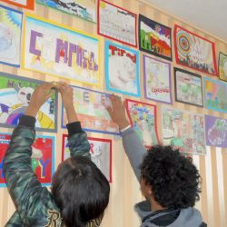 students hanging artwork
