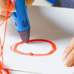 Kid hands with 3d printing pen, colorful filaments on white desk
