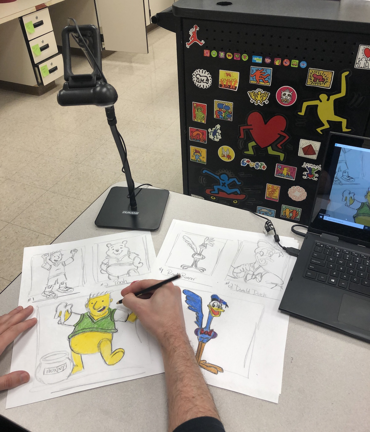 teacher drawing in front of a desk