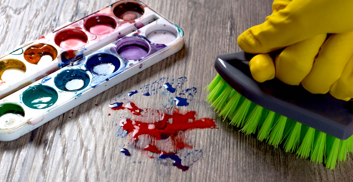The woman brushing the stain from the paint. Clean up, wash. A mess. A gloved hand wipes the stain from the paints.The woman does the cleaning. Clean, house, housekeeper, cleanup and housework.