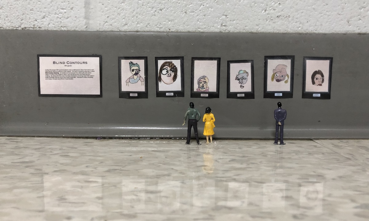 miniature figures looking at art