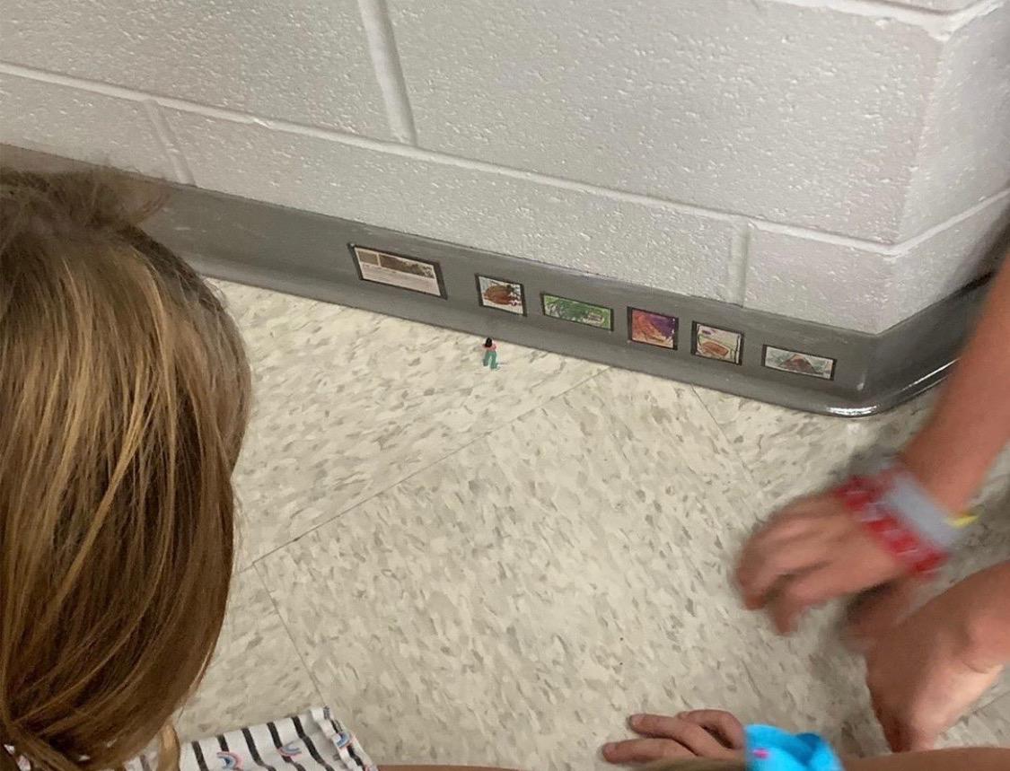 Students looking at tiny art display