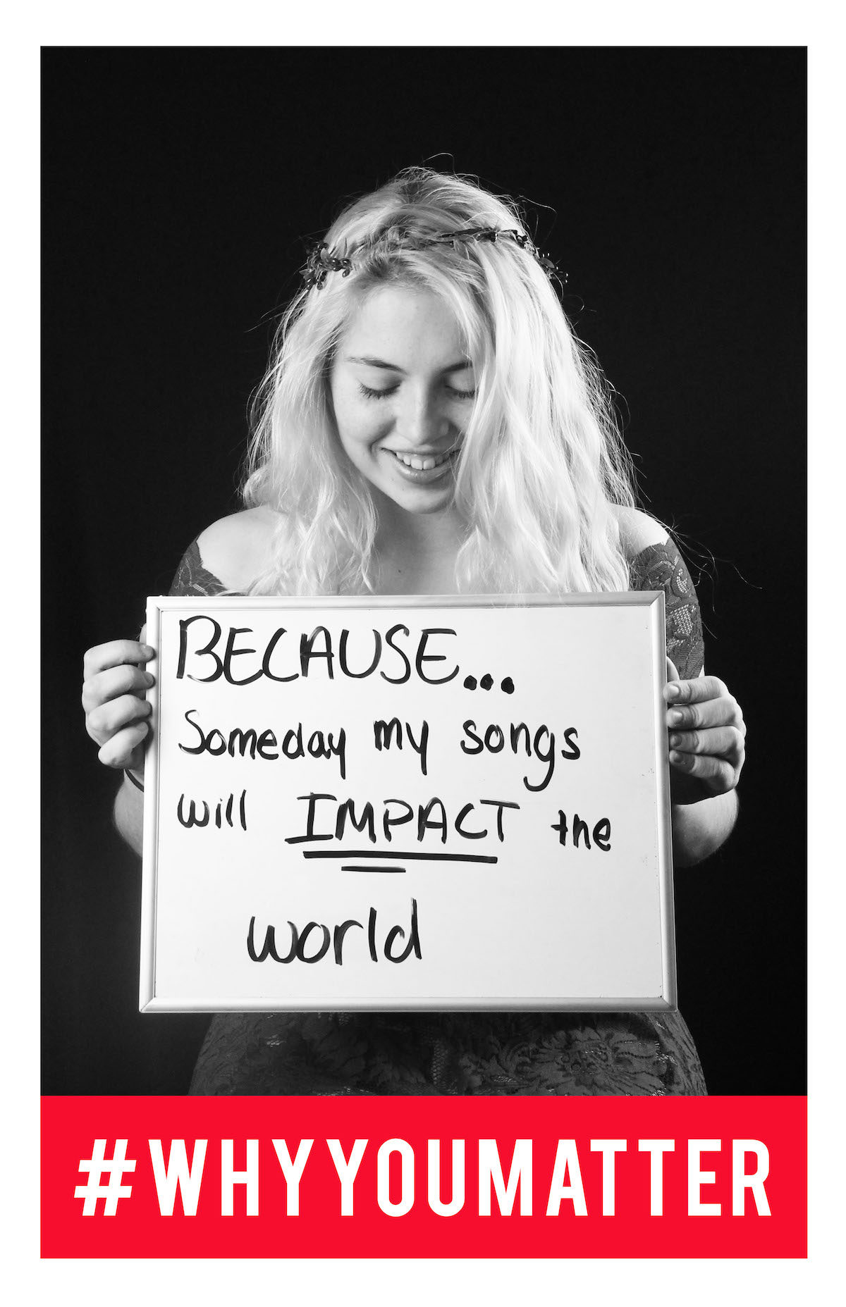 student holding sign that says 'because someday my songs will impact the world.'