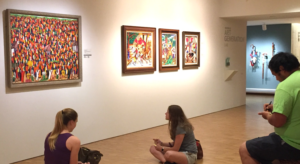 students looking at colorful artwork in a musem